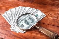 Dollari e lente d'ingrandimento Fotografia Stock Libera da Diritti