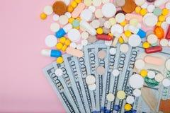Dollari e pillole su un fondo rosa La medicina di prescrizione sui dollari per il concetto dell'industria farmaceutica di alto co Fotografie Stock Libere da Diritti
