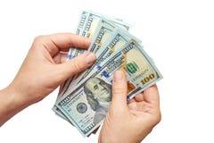 Dollari in mani su un fondo bianco Immagine Stock