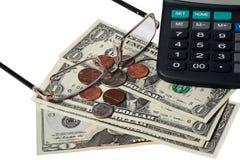 Dollari, monete, vetri e calcolatore disposti su una tavola immagine stock