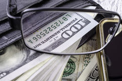 Dollari in portafoglio nero attraverso i vetri Fotografia Stock Libera da Diritti
