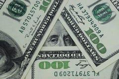 100 dollari sono sistemati sotto forma di triangolo Fotografie Stock