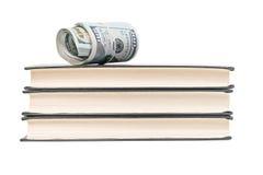 Dollari su un mucchio dei libri Fotografie Stock