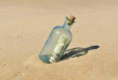 10 dollari in una bottiglia sulla sabbia Fotografia Stock