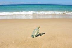 10 dollari in una bottiglia sulla spiaggia Fotografie Stock Libere da Diritti