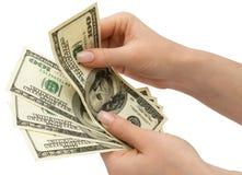 Dollari US In mano della donna, isolata con il residuo della potatura meccanica Fotografia Stock Libera da Diritti