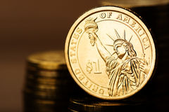 Dollarmuntstuk en gouden geld op het bureau Stock Foto's
