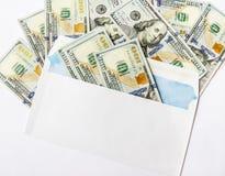 Dollarna i ett kuvert isoleras på en vit bakgrund royaltyfri fotografi