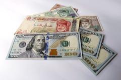 Dollaro americano e riyal di abitante dell'Oman su fondo bianco Immagini Stock
