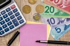 Dollaro canadese con la penna ed il calcolatore del blocco note fotografia stock libera da diritti
