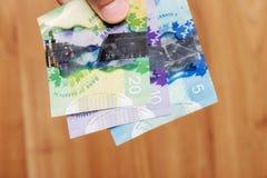 Dollaro del Canada con fondo ed il dito di legno dell'uomo Immagine Stock