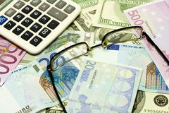 Dollaro, euro banconote, calcolatore e vetri Fotografia Stock Libera da Diritti