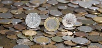 Dollaro, euro e franco su fondo di molte vecchie monete Fotografia Stock