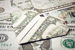 Dollarorigamiherz im Banknotenhintergrund Moneygami Stockbilder