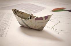 Dollarpapierboot auf Finanzdaten Stockfotografie