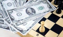 Dollarpengar och schack royaltyfria bilder