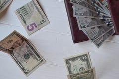 Dollarpengarsedlar och plånbok på den vita träbakgrunden amerikansk valuta isolerad fjärdedelwhite 5000 roubles för modell för ba Arkivfoto