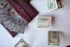 Dollarpengarsedlar och plånbok på den vita träbakgrunden amerikansk valuta isolerad fjärdedelwhite 5000 roubles för modell för ba Royaltyfri Foto