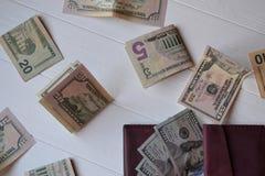 Dollarpengarsedlar och plånbok på den vita träbakgrunden amerikansk valuta isolerad fjärdedelwhite 5000 roubles för modell för ba Royaltyfri Bild