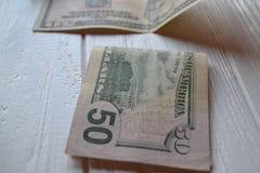 Dollarpengarsedlar på den vita träbakgrunden amerikansk valuta isolerad fjärdedelwhite 5000 roubles för modell för bakgrundsbills Arkivbild