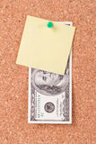 Dollarräkning och klibbig stolpe på Cork Board Royaltyfri Foto