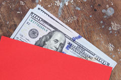 Dollarräkningar eller pengar med det röda kuvertet Arkivbild