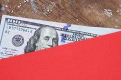 Dollarräkningar eller pengar med det röda kuvertet Royaltyfria Foton