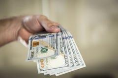 100 dollarräkningar i en hand för man` s Royaltyfri Fotografi