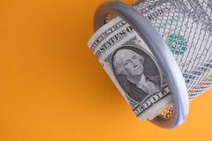 Dollarräkningar i en soptunna på en gul bakgrund Fotografering för Bildbyråer