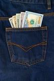Dollarräkningar i facket av jeans Arkivfoto
