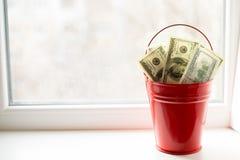 Dollarräkningar i röd hink på det vita fönstret Ljus bakgrund placera text Top beskådar mycket pengar fotografering för bildbyråer