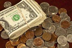 Dollarräkningar och blandade mynt som alla showkläder arkivfoton