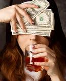 Dollarräkningar och exponeringsglas för nunna hållande med alkohol på mörk bakgrund kvinnahanden med snitt stängde ögon och drack Arkivfoto