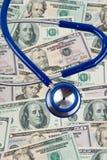 Dollarräkningar och stetoskop Arkivfoto