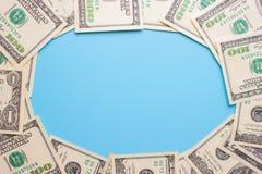 100 dollarräkningar på den blåa bakgrunden Arkivfoto