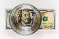 100 dollarräkningar som är bak exponeringsglas Arkivfoto