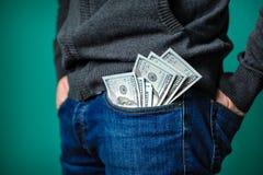 Dollarräkningar som klibbar ut ur facket av en man Arkivfoto