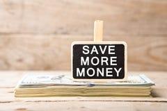 Dollarräkningar, svart tavla med text & x22; SPARA MER MONEY& x22; Royaltyfria Bilder
