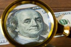 100 dollarrekening onder een vergrootglas op een houten lijst E Stock Foto