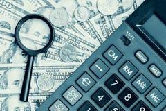 Dollarrekeningen met een calculator en een vergrootglas Stock Foto's