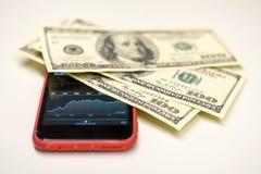 Dollarrekeningen over een smartphone met voorradengrafiek royalty-vrije stock afbeelding