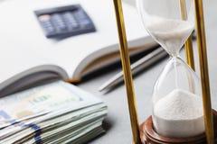 Dollarrekeningen, zandloper en notitieboekje voor de planning van investeringen of contant gelduitgaven royalty-vrije stock afbeeldingen