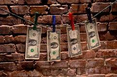 Dollarräkningar som hänger på rep Arkivfoto