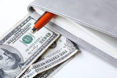Dollars américains d'argent avec le livre Image libre de droits