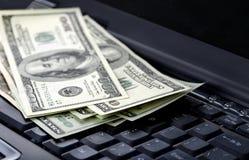 Dollars américains sur l'ordinateur portatif Photo stock