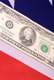 Dollars on american flag Stock Images