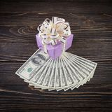 Dollars anf gift box on wooden background Stock Photos