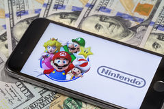 Dollars and Apple iPhone 6s with Super Mario Bros figure charact Royalty Free Stock Image