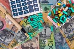 Dollars australiens avec le chariot complètement des pilules, du stylo et de la calculatrice image stock