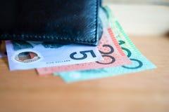 Dollars australiens 5, 20, 100 notes du dollar et factures à côté de portefeuille noir au foyer sélectif $ Photos libres de droits